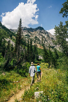 Caucasian couple hiking on path in mountains - BLEF03197