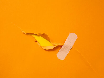 First aid adhesive plaster on torn orange paper - CUF51130