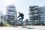 Man cycling past multi-storey building, Milan, Lombardia, Italy - CUF51148