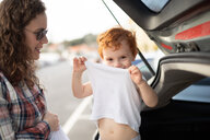 Boy getting fresh change of clothes at car boot - CUF51166