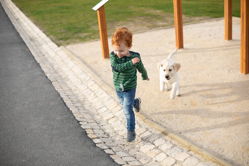 Boy running away from pet puppy - CUF51172