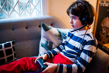 Boy sitting on sofa wearing headset and using game controller - CUF51187