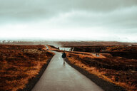 Tourist walking on road leading to Godafoss waterfall, Akureyri, Eyjafjardarsysla, Iceland - CUF51211