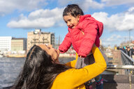 Mother lifting daughter in mid air by river, Berlin, Germany - CUF51271