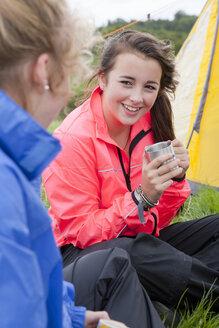 Close up of smiling girls drinking tea next to tent - JUIF00908