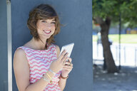 Portrait of smiling young woman using digital tablet - JUIF00917