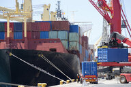 Cranes unloading container ship at commercial dock - JUIF00923
