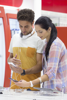 Couple looking at cell phones in electronics store - JUIF00929