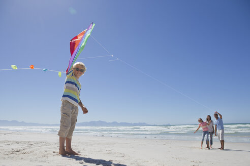 Portrait of smiling boy holding kite on sunny beach - JUIF00932