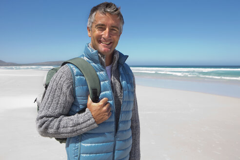 Portrait of smiling man with backpack on sunny beach - JUIF00959
