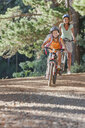 Mother and daughter riding mountain bikes in woods - JUIF00965