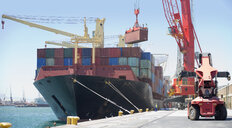 Crane unloading container ship at commercial dock - JUIF00995