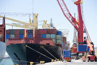 Crane unloading container ship at commercial dock - JUIF00998