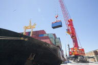Crane unloading container ship at commercial dock - JUIF01007