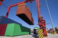 Crane lifting cargo container at commercial dock - JUIF01010