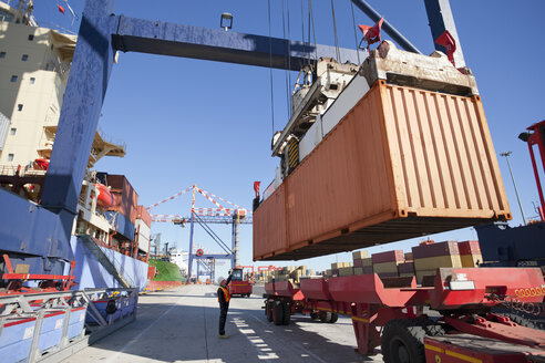 Crane unloading container ship at commercial dock - JUIF01013
