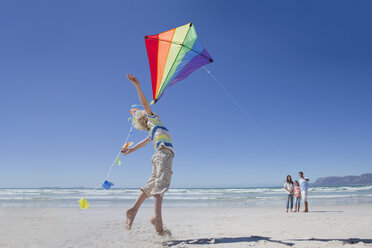 Boy jumping and reaching for kite on sunny beach - JUIF01019