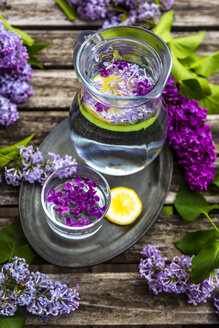 Jar with glass of water with lilac sirup and lemon - SARF04259