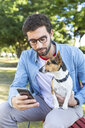 Portrait of young man sitting on park bench with his dog looking at  smartphone - WPEF01504