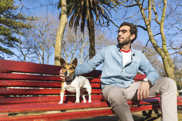 Content young man sitting on park bench stroking his dog - WPEF01516