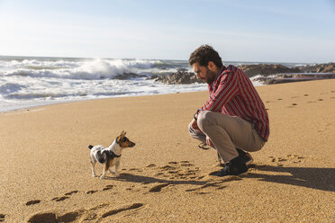 Portugal, Porto, young man playing on the beach with his dog - WPEF01519