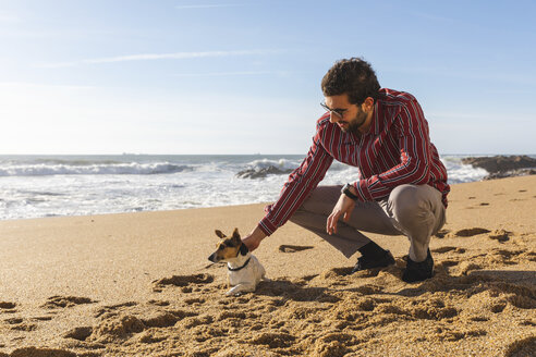 Portugal, Porto, young man stroking his dog on the beach - WPEF01522