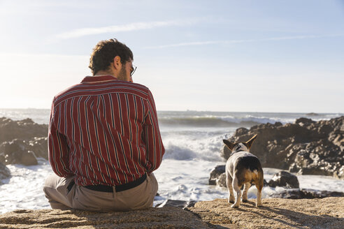 Portugal, Porto, back viwe of young man and his dog in front of the sea - WPEF01528