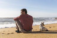 Portugal, Porto, back view of young man sitting on the beach with his dog - WPEF01531