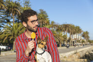 Young man with dog eating ice lolly - WPEF01534