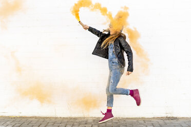 Girl with orange smoke torch jumping in the air - ERRF01275