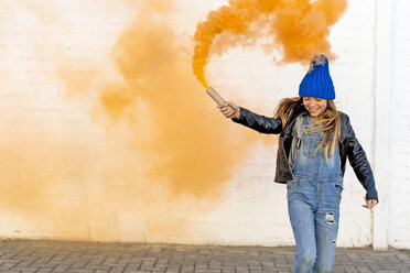 Smiling girl with orange smoke torch on the street - ERRF01278