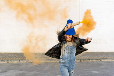 Smiling girl with orange smoke torch on the street - ERRF01281