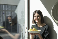 Smiling young woman standing at the window in sunshine holding a plate of salad - AHSF00359