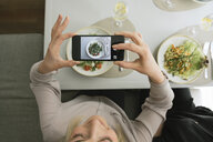 Young woman taking a cell phone picture of a salad in a restaurant - AHSF00377