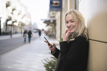 Portrait of smiling young woman with cell phone in the city - AHSF00386