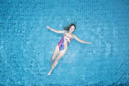 Young woman floating on water in swimming pool - STBF00345