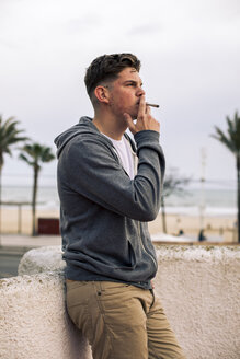 Young man smoking a joint with palm trees in the background - ACPF00509