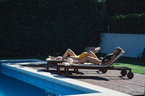 Two beautiful women sunbathing on a terrace next to the pool - OCMF00451
