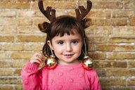 Portrait of smiling toddler girl wearing reindeer antlers headband and Christmas baubles - GEMF02942