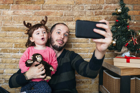 Portrait of father and little daughter taking selfie with smartphone at Christmas time - GEMF02945