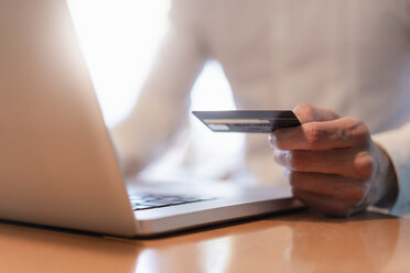 Man's hands holding credit card and while making an online payment with laptop, close-up - DIGF07018