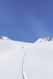 Österreich, Tirol, zwischen Ischgl und Galtür, eine Skitourengeher steigt im Tiefschnee auf zum Gipfel der Hohen Köpfen - MMAF00934