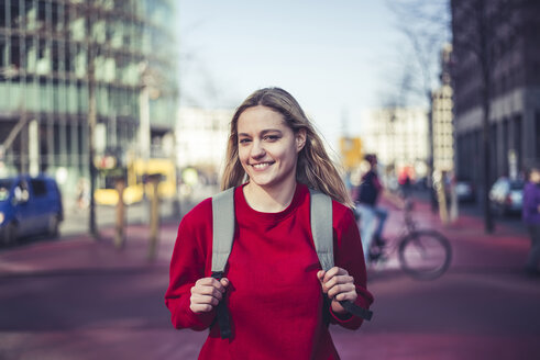 Germany, Berlin, portrait of smiling young woman with backpack in the city - BFRF02019