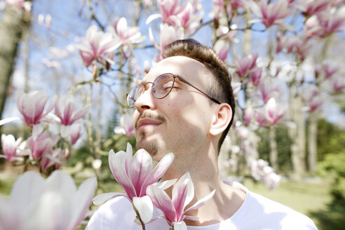 Young man enjoying magnolia blossom - KMKF00939