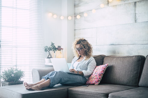 Woman using laptop on couch at home - SIPF01958