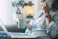 Close-up of woman on couch at home with coffee mug, laptop and cell phone - SIPF01964