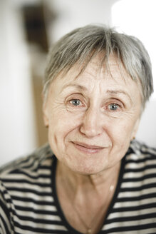 Portrait of happy senior woman with short hair, smiling with tears in her eyes - KMKF00958