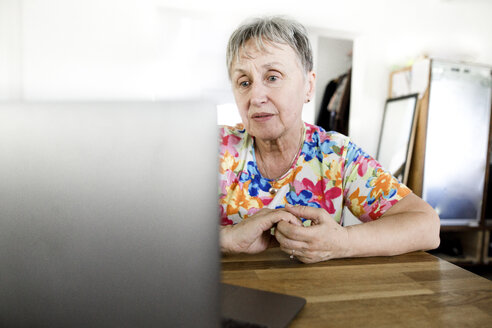 Senior woman sitting at table at home using laptop - KMKF00962