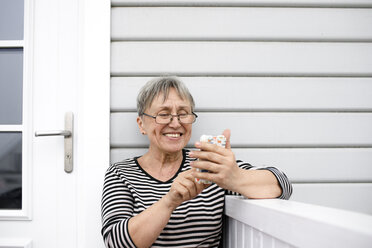 Happy senior woman using cell phone on porch of her house - KMKF00965