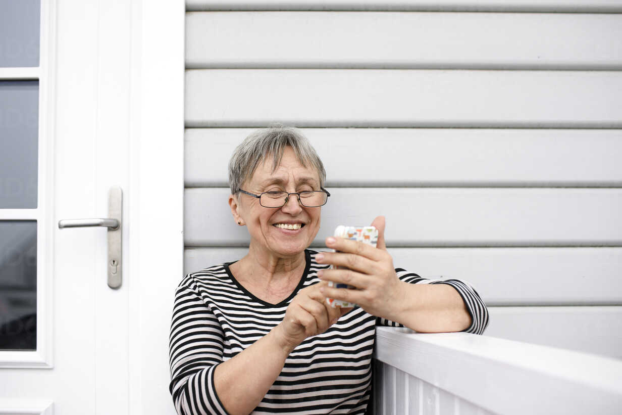 Happy senior woman using cell phone on porch of her house - KMKF00965 - Katharina Mikhrin/Westend61